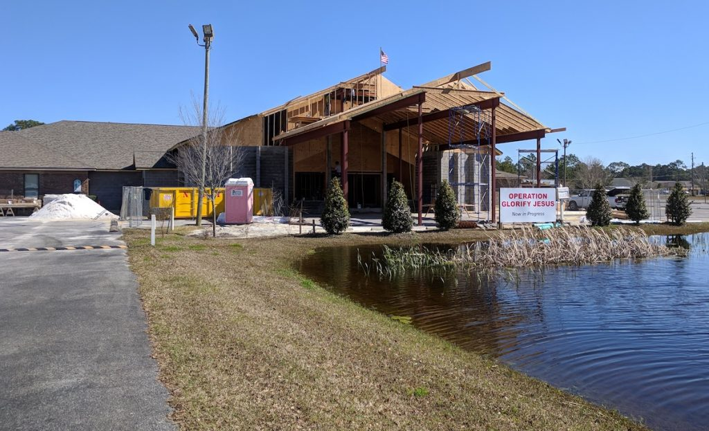 View from across the pond of the structural steel in place at Emerald Coast Fellowship in Lynn Haven, Florida